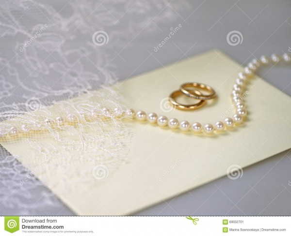 Convite do casamento com uma colar da pérola e uns anéis dourados