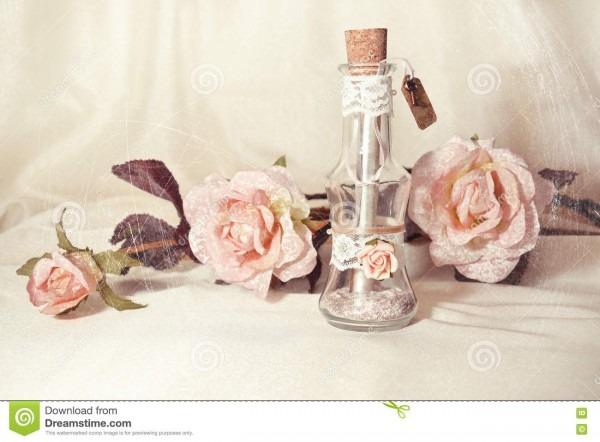 Convite do casamento em uma garrafa de vidro e em umas rosas cor