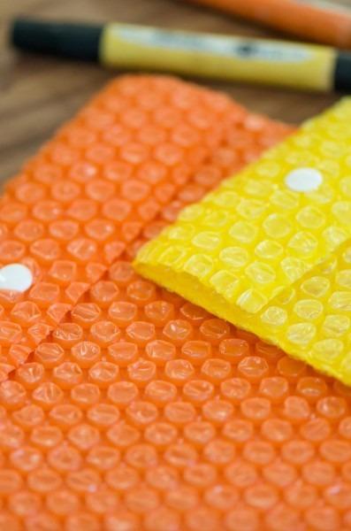 Envelope em plastico bolha colorido com botão de pressão